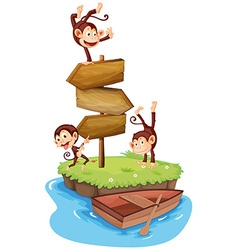 Three monkeys and wooden signs on island vector image vector image
