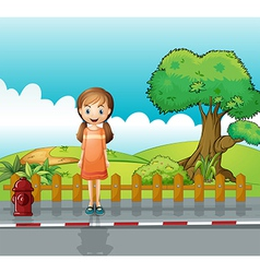 A small girl standing near the wooden fence vector image