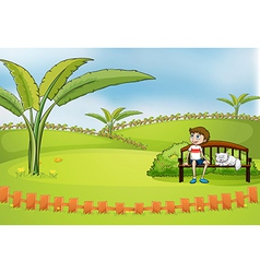 A boy sitting in the park with his pet vector image