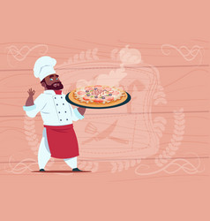 African american chef cook holding pizza smiling vector