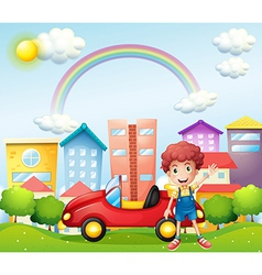 A boy and his red car near the high buildings vector image vector image