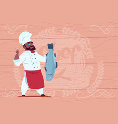 African american chef cook hold fish smiling vector