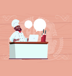 African american chef cook working at laptop vector
