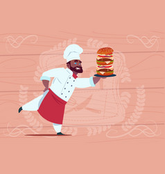 African american chef cook hold big burger smiling vector