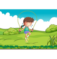 A girl playing jumping rope at the top of the hill vector