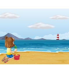 A young girl playing with the sand in the beach vector