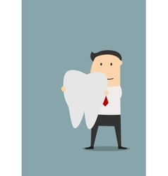 Businessman holding a large white tooth vector image