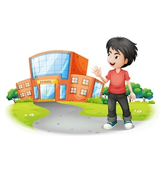 A boy standing in front of the school vector