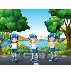 Three girls riding bike on the road vector image