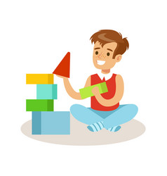 Happy boy sitting and playing with colorful cubes vector