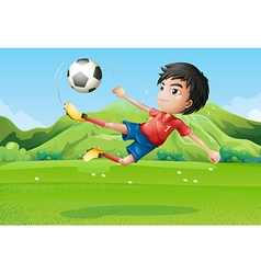 A young boy playing football at the field vector image vector image