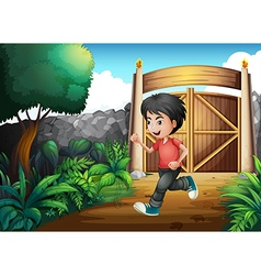 A boy with a red shirt running inside the fence vector image