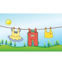 Kids clothes hanging under the sun vector