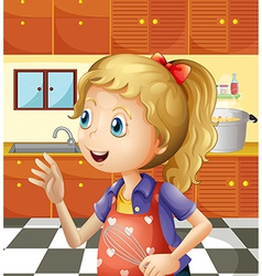 A young girl at the kitchen holding a mixer vector