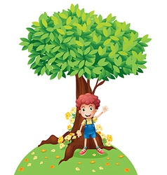 A young boy standing under a big tree vector image
