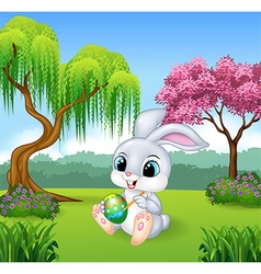 Cartoon little bunny painting an egg vector