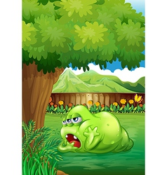 A tired green monster near the tree vector image vector image