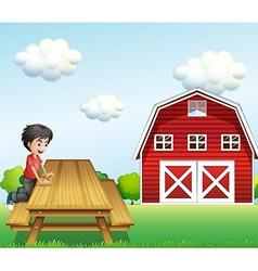 A boy at the table near the barnhouse vector