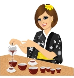Attractive woman in black kimono pouring tea vector