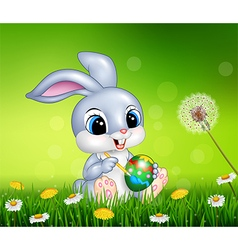 Easter bunny painting an egg on grass background vector
