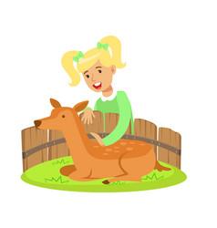 Cute little girl petting lying deer in a mini zoo vector