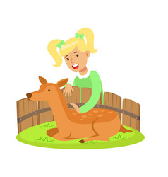 Cute little girl petting lying deer in a mini zoo vector