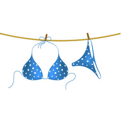 Bikini suit with white dots hanging on rope vector