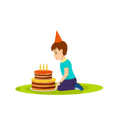 Little boy in festive mood blows out birthday cake vector