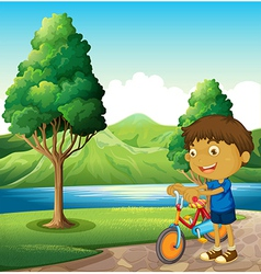 A kid at the riverbank playing with his bicycle vector