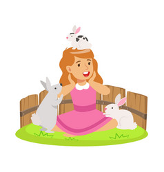 Happy smiling girl playing with small rabbits in a vector