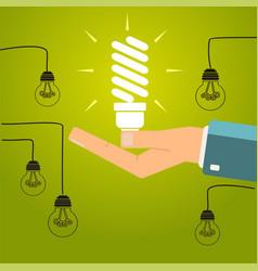 Hand holding a bright energy saving light bulb vector