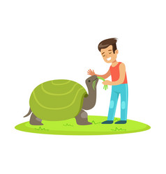 Happy little girl feeding with grass a huge turtle vector