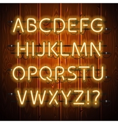 Glowing neon alphabet on wooden background vector