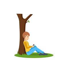 Boy listening to music near tree in the park vector