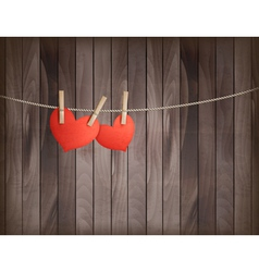 Two hearts hanging on a rope in front of wooden vector