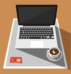Laptop credit card and cup of coffee on desk vector
