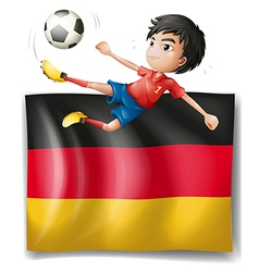 A boy playing soccer in front of the flag of vector image