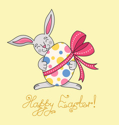 Easter bunny is holding egg in paws vector