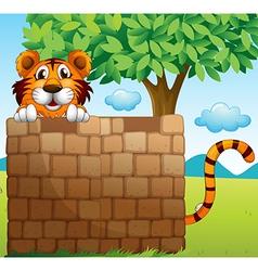 A tiger hiding on a pile of bricks vector