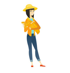 Young asian farmer holding hay in hands vector