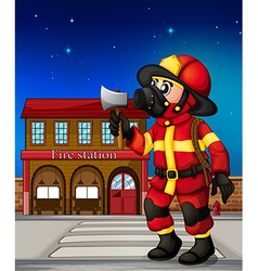 A fireman holding an ax outside the fire station vector image