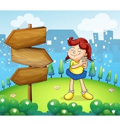A little girl standing beside the wooden arrow vector image