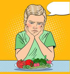 Pop art upset boy with plate of fresh vegetables vector