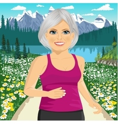 Senior woman jogging among mountains vector