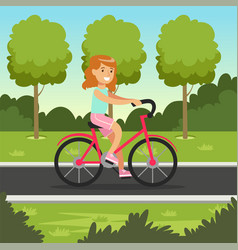 smiling redhead girl cycling on bicycle in the vector image