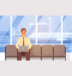 man sitting in airport hall using laptop computer vector image