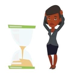Desperate businesswoman looking at hourglass vector