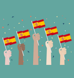 Hands holding up spain flags vector
