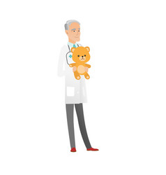 Senior caucasian pediatrician holding teddy bear vector