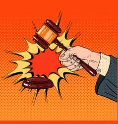 Pop art judge hand hitting wooden gavel vector